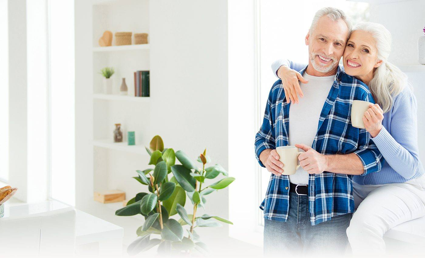 Smiling older man and woman holding coffee mugs