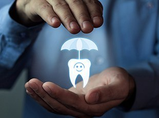 Hands holding animated tooth under an umbrella