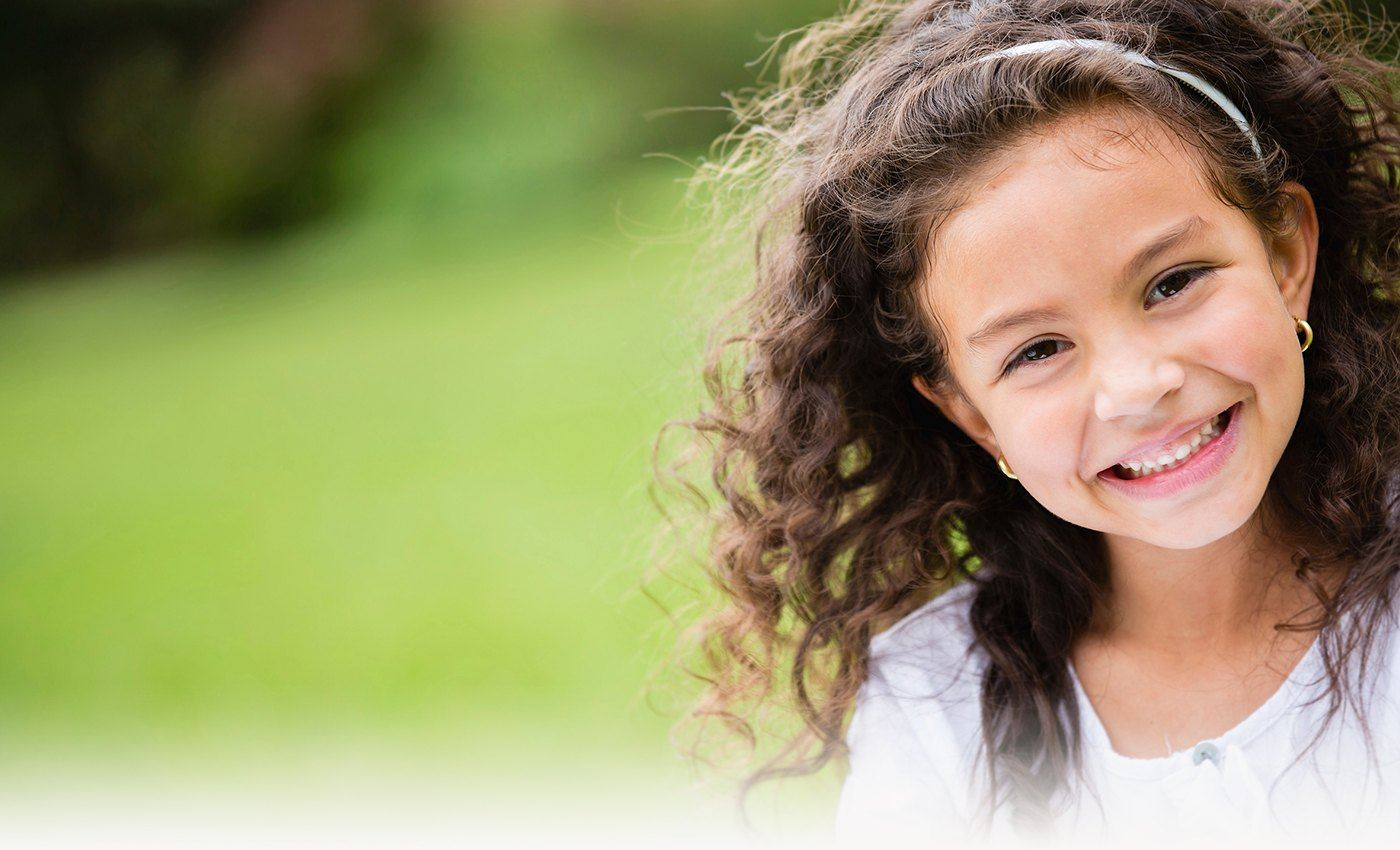Little girl smiling outdoors