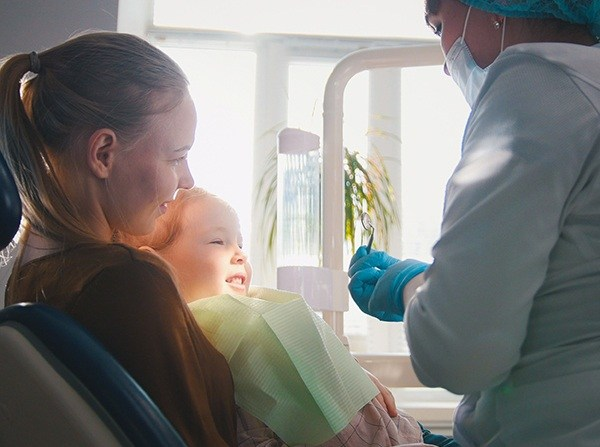 Mother with child in lap during dental treatment