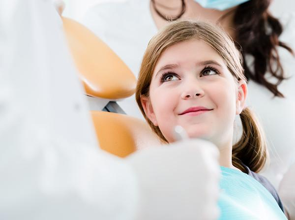 Child in dental chair smiling at dentist