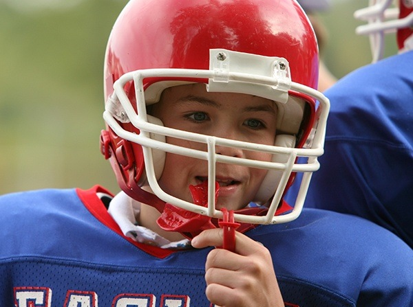 Teen boy in football helmet with red mouthguard