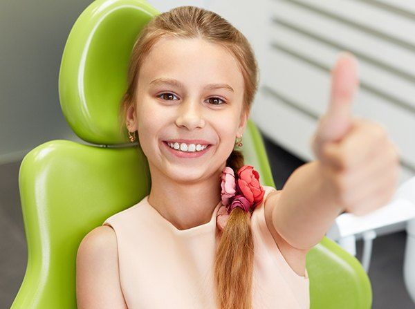 Little girl in dental chair giving thumbs up