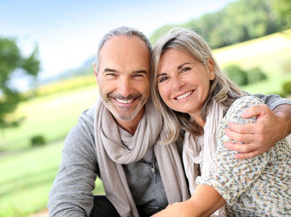 Older man and woman outdoors smiling