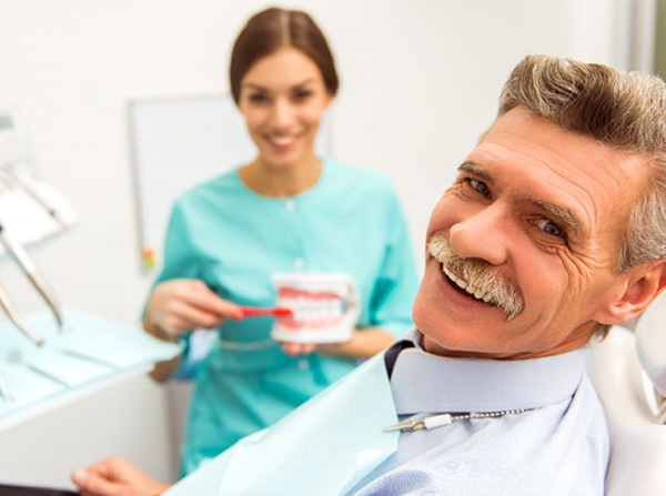 Older man with mustache smiling in dental chair