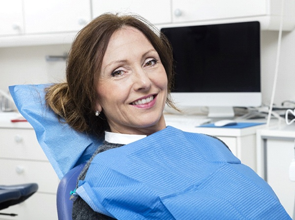 Middle-aged woman with brown hair smiling in dental chair