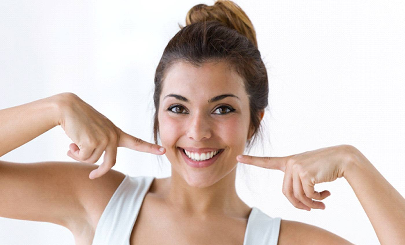 A young female wearing a white sleeveless blouse and pointing to her smile after receiving in-practice teeth whitening in Leesburg, VA