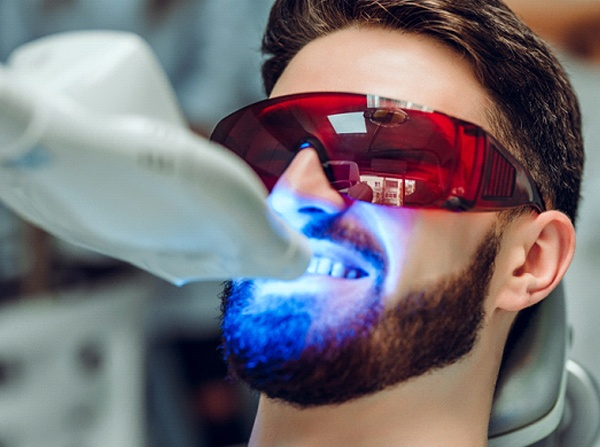 A young male with a beard wearing protective eyewear while receiving in-practice teeth whitening