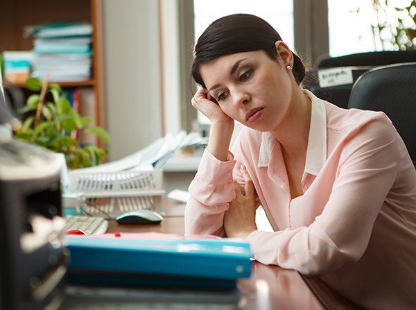 Tired woman at desk with head resting on hand