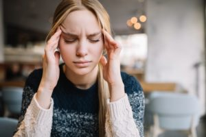 Blond woman suffering from migraines and TMJ in Leesburg