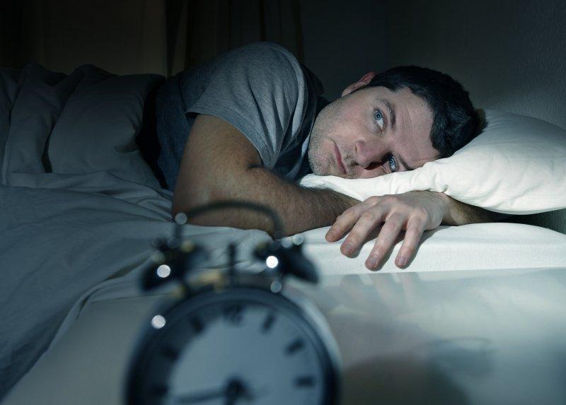 Man lying awake in bed looking at alarm clock