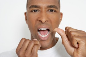 Man brushing and flossing teeth