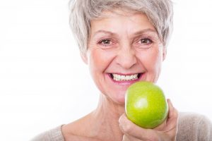 Woman with dental implants in Leesburg holding an apple.
