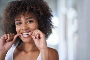 young woman flossing dental implants